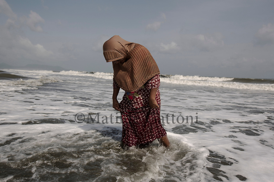 "Indonesia – Sumatra – Banda Aceh – Alue Naga – Nurmalawati, 41-year-old walking along the beach of her neighborhood. Nurmalawati was spending her Sunday morning at home, together with her husband and niece, feeding her eight-month-old son. Suddenly, the earthquake shook the village and the water of the ocean started receding. ""That was the last time I saw my husband and my kid alive"" she says."