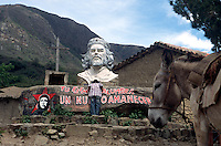 "A student visitor from the regional city of Santa Cruz de la Sierra examines a plaque on a bust of Ernesto ""Che"" Guevara in La Higuera, Bolivia, Saturday, Nov. 13, 2004. Guevara was captured by the Bolivian army in 1967 in a nearby valley and executed in La Higuera days later. Guevara and fellow communist guerillas were attempting to launch a continent-wide revolution modeled on Guevara's success in Cuba in the late 1950s. The Bolivian government recently began promoting the area where he fought, was captured, killed and burried for 30 years as the ""Ruta del Che,"" or Che's Route. (Kevin Moloney for the New York Times)"