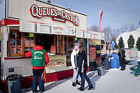 """Carnaval-goer looks at the """"Queues de Castor"""" (beaver tails) stand at the Quebec Winter Carnival (Carnaval de Quebec) in Quebec city, February 3, 2010. With close to one million participants, it has grown to become the third largest winter celebration in the world."""