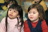 Two girls listen to a story at a Chinese nursery in Camden Town, London.