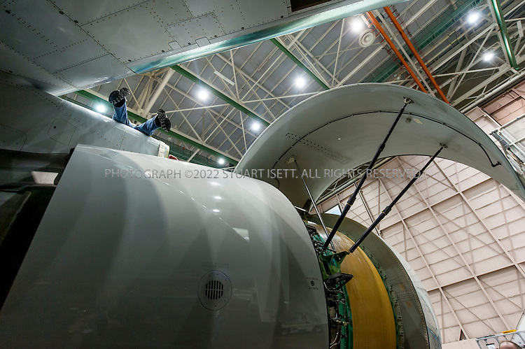 3/7/2012----Everett, WA, USA..A Boeing employee, upper left, works on a Boeing 767 Cargo's engine...The Boeing 767 is a mid-size, wide-body twin-engine jet airliner built by Boeing Commercial Airplanesnwas first flown in 1982. The aircraft features two turbofan engines, a conventional tail, and for reduced aerodynamic drag, a supercritical wing design. Designed as a smaller wide-body airliner than preceding aircraft such as the 747, the 767 has a capacity of 181 to 375 persons and a range of 3,850 to 6,385 nautical miles (7,130 to 11,825 km), depending on variant. Development of the 767 occurred in tandem with a narrow-body twinjet, the 757, resulting in shared design features which allow pilots to obtain a common type rating to operate both aircraft. (SOURCE: WIKIPEDIA)..Boeing recently won a large airforce tanker order of the 767 which will keep production of the aircraft join for the foreseeable future...©2012 Stuart Isett. All rights reserved