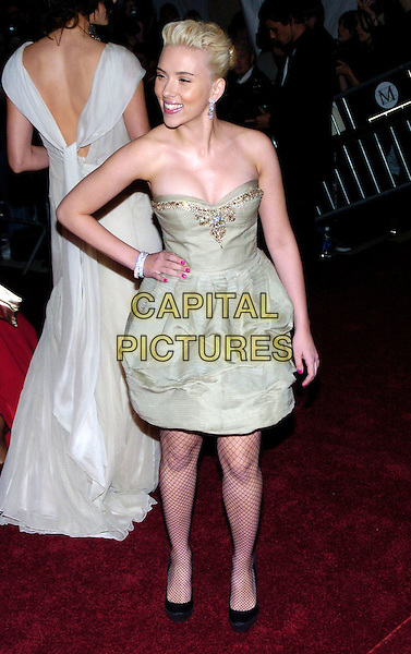 "SCARLETT JOHANSSON.2007 Metropolitan Museum of Art Costume Institute Gala celebrating ""Poiret: King of Fashion"" exibition at the Metropolitan Museum of Art, New York City, New York, USA..May 7th, 2007.full length beige strapless dress black shoes fishnet hand on hip stockings tights gold trim.CAP/ADM/BL.©Bill Lyons/AdMedia/Capital Pictures *** Local Caption ***"