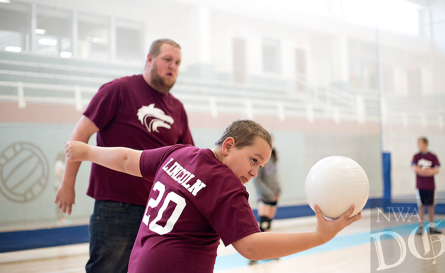 NWA Democrat-Gazette/JASON IVESTER --01/20/2015--<br /> Lincoln Middle School coach Ryan Acord (cq) watches as Lincoln sixth-grader JW Alexander serves the ball on Tuesday, Jan. 20, 2015, inside the Jones Center for Families in Springdale. Dustin and other athletes were participating in the Special Olympics Arkansas Area 3 Unified Volleyball Competition at the center.