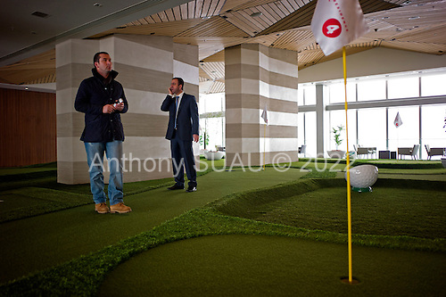 Istanbul, Turkey<br /> March 9, 2011<br /> <br /> Kiler Holding Chairman Nahit Kiler (center) stops to plays gulf to take a business call on the Sapphire's 40th floor golf course. Mr. Kiler is owner of the Sapphire building, a skyscraper, (the tallest building in Europe) located in Istanbul's Levent business district. It is a luxury shopping and residence mixed-use project by Biskon Construction (a subsidiary of the Kiler group of companies). Sapphire Istanbul offers a luxurious life style to owners as upper floor apartments sell for as high as $7,500,000 US.