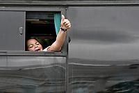 CALI - COLOMBIA, 14-04-2020: Una mujer hace señal de victoria para despedirse y dar gracias a los colombianos desde un bus durante la jornada de repatriación de 215 venezolanos hacía su país desde Cali en el día 22 de la cuarentena total en el territorio colombiano causada por la pandemia  del Coronavirus, COVID-19. / A woman raises her thumb in victory to say goodbye and give thanks to the Colombians from the bus during the repatriation journey of 215 Venezuelans to their country from Cali during the day 22 of total quarantine in Colombian territory caused by the Coronavirus pandemic, COVID-19. Photo: VizzorImage / Gabriel Aponte / Staff