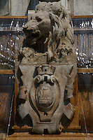 A particular of the fountain in place Saint Sulpice in Paris, with water, in a sunny spring day: A majestic aggressive sculpted lion which holds the coat of arm of the town, which represents a vessel. The water was just starting to drop into the lower basin. Digitally Improved Photo.