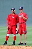 Second baseman Yoan Moncada (24) of the Greenville Drive, left, talks with coach Laz Gutierrez before a game against the Lexington Legends on Monday, May 18, 2015, at Fluor Field at the West End in Greenville, South Carolina. Moncada, a 19-year-old prospect from Cuba, made his professional debut tonight in the Red Sox organization. (Tom Priddy/Four Seam Images)