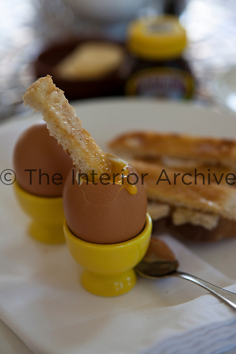 Boiled eggs in yellow egg cups with buttered toast soldiers