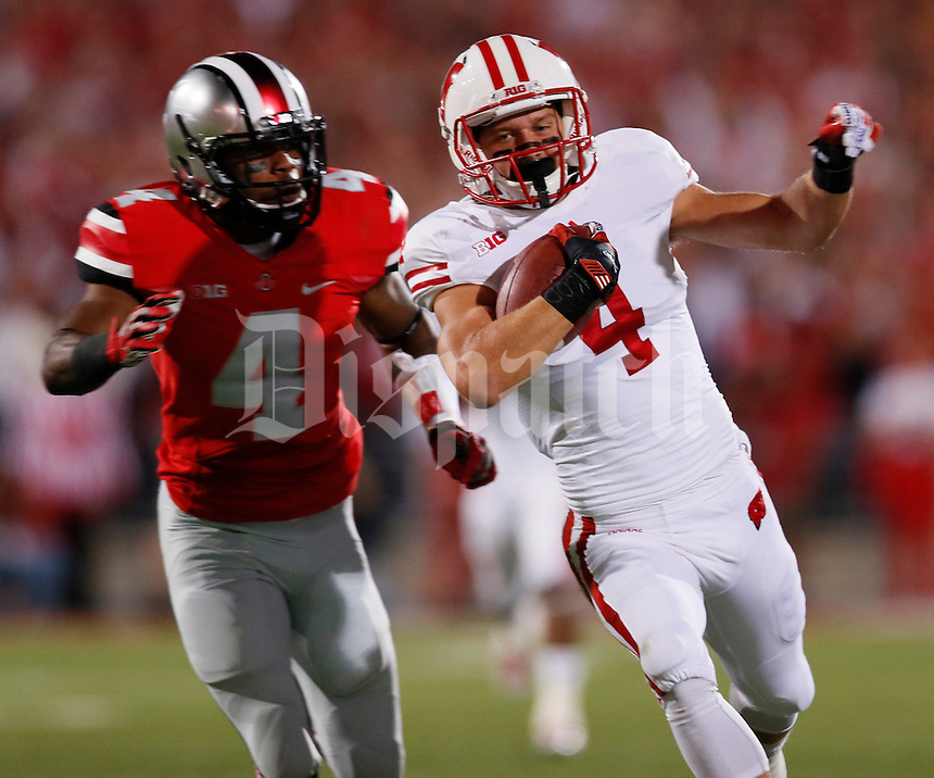 Wisconsin Badgers wide receiver Jared Abbrederis (4) is pursued by Ohio State Buckeyes safety C.J. Barnett (4) during Saturday's NCAA Division I football game at Ohio Stadium in Columbus on September 28, 2013. (Barbara J. Perenic/Columbus Dispatch)