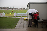Prestatyn Town 0 Port Talbot Town 0, 19/10/2013. Bastion Gardens, Welsh Premier League. A group of spectators huddling under an umbrella at Bastion Gardens during during half-time of the match between Prestatyn Town and visitors Port Talbot Town in the Welsh Premier League. Prestatyn Town were Welsh Cup winners in 2013. The match ended goalless and was watched by 211 spectators. Photo by Colin McPherson.
