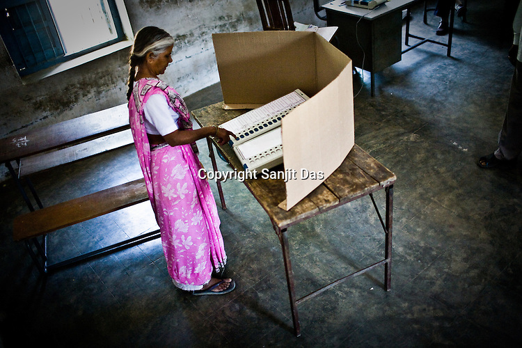 A voter is seen casting her vote on the electronic polling machine in a polling booth in Government school building in Ghuma village of Rural Ahmedabad, Gujarat India. About 49 per cent of the 3.65 crore electorate today exercised their franchise in the single phase polling in the state's 26 Lok Sabha constituencies on April 30th 2009.