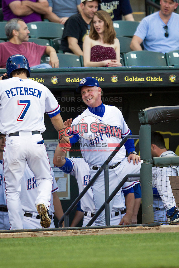 Round Rock Express manager Steve Buchele #22 smiles as he greets outfielder Bryan Petersen #7 after he scored a first inning run in the Pacific Coast League baseball game against the Memphis Redbirds on April 24, 2014 at the Dell Diamond in Round Rock, Texas. The Express defeated the Redbirds 6-2. (Andrew Woolley/Four Seam Images)
