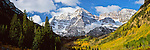 Capped with snow in late September, the Maroon Bells of Colorado stand above a glacial valley--already in the midst of an atuumn transformation as the aspen trees change to a golden yellow.<br /> Snowmass Wilderness Area, Colorado