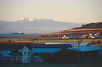 Puget Sound, Ebey's Landing National Historical Reserve, Whidbey Island, Washington State, Pacific Northwest, USA, farms preserved by the purchase of development rights carpet Ebey's Prairie at sunrise, a container ship inbound on Puget Sound, Olympic Mountains in the distance,.