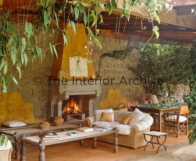 The terrace is divided into summer living and dining areas either side of a central fireplace