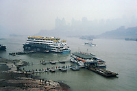 Ferry passengers are disembarking from a ferry across the Yangtze River in Chongqing, China. Downtown highrise buildings at the back appears through typical Chongqing pollution haze..15 May 2007