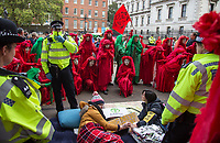 The Red Brigade, also known as the Invisible circus with 2 protesters who clued themselves together.<br /> .<br /> Environmental activists from Extinction Rebellion protest in London on 09 October 2019 in London, England.<br /> .<br /> Protesters plan to blockade the London government district for a two week period, as part of 'International Rebellion' taking place in over 60 cities around the world, calling for decisive and immediate action from governments in the face of climate and ecological emergency. <br /> .<br /> Photo by Andy Rowland.