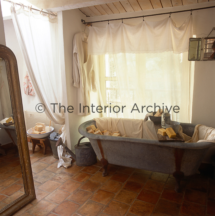 A rustic room with a terracotta floor. The room is arranged like a bathroom with an old freestanding bath filled with blocks of soap. A sheer curtain hangs at the window.
