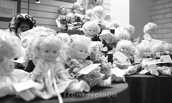 One black doll amidst a group of white dolls, ZCMI, University Mall.<br />