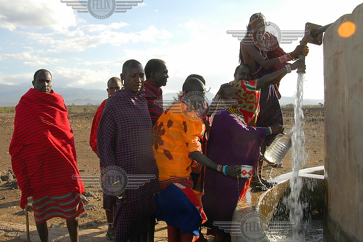 People from a Maasai tribe collect water from a well and tap close to the Amboseli National Park....