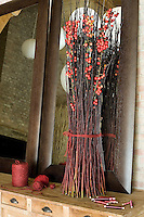 Tall cut stems decorated with red berries are displayed informally on an antique chest of drawers
