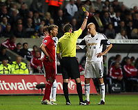Pictured: Referee Michael Oliver (C) shows a yellow card to Jonjo Shelvey (R) of Swansea and Lucas Leiva (L) of Liverpool.<br />