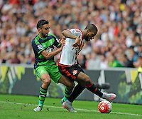 Neil Taylor of Swansea City (left) challenges Jermain Lens of Sunderland during the Barclays Premier League match between Sunderland and Swansea City played at Stadium of Light, Sunderland