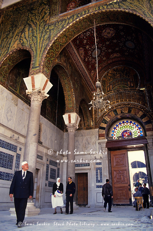 People walking under a decorative ceiling while entering the Umayyad Mosque, Damascus, Syria.