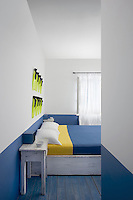 The bedroom has an eye catching blue and white colour scheme with splashes of yellow and distressed wooden furniture