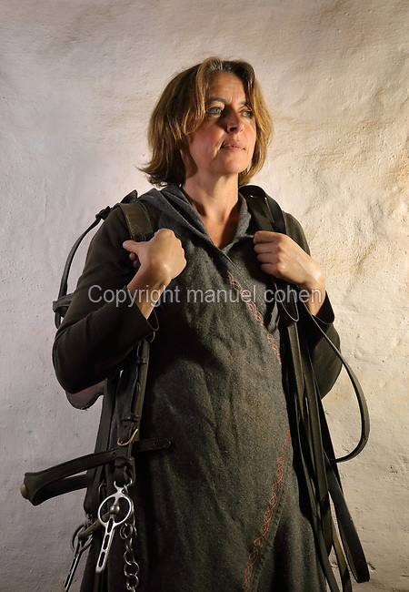 Laetitia Roux, carter on the Guedelon project since 01/04/2004, wearing medieval costume and carrying a bridle and reins, at the Chateau de Guedelon, a castle built since 1997 using only medieval materials and processes, in Treigny, Yonne, Burgundy, France. Carts pulled by cows or horses are used at Guedelon to transport building materials around the site. The Guedelon project was begun in 1997 by Michel Guyot, owner of the nearby Chateau de Saint-Fargeau, with architect Jacques Moulin. It is an educational and scientific project with the aim of understanding medieval building techniques and the chateau should be completed in the 2020s. Picture by Manuel Cohen