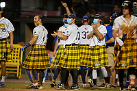 Savannah Bananas Bill Leroy (1), Cole Frederick (13), and John Michael Faile (21) celebrate a hit during a Coastal Plain League game against the Macon Bacon on July 15, 2020 at Grayson Stadium in Savannah, Georgia.  Savannah wore kilts for their St. Patrick's Day in July promotion.  (Mike Janes/Four Seam Images)