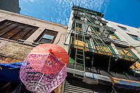 New York, NY - 7 July 2014 - Souvenir umbrellas against an empty boarded up loft building on Canal Street. ©Stacy Walsh Rosenstock/Alamy