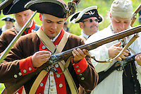 Continental Army soldier primes the pan of the flintlock with a powder cartridge as he reloads his musket during a Revolutionary War re-enactment at Fort Ticonderoga, New York, USA.