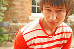 Portrait close up of serious intent teenage boy, outdoors with brick building  in background UK