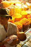 VIETNAM, Saigon, Ben Thanh Market, a girl sleeps in her mothers arms in front of the dried shrimp section of the market, Ho Chi Minh City
