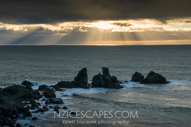 Sunrays penetrating clouds viewed from Cape Foulwind near Westport, West Coast, Buller Region, New Zealand