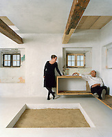 Jutta Görlich and Peter Haimerl relax in the living room of their restored country house in Viechtach, Bavaria where original features such as a large firepit have been preserved