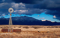 A ranch windmill on a desert plain, with the Dos Cabezas montains in the background as storm clouds gather overhead. Arizona.