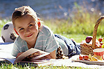 Young girl (8 years old) reading a book lying down on a blanket at a picnic summer reading Lake Pleasant Bothell Washington State USA MR.