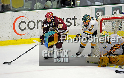9 January 2009: Boston College forward and Team Captain Brock Bradford (19), a Senior from Burnaby, BC, rounds the net while being pursued by University of Vermont Catamount Brian Roloff (14) during the first game of their weekend series at Gutterson Fieldhouse in Burlington, Vermont. The Catamounts scored with one second remaining in regulation time to earn a 3-3 tie with the visiting Eagles. Mandatory Photo Credit: Ed Wolfstein Photo