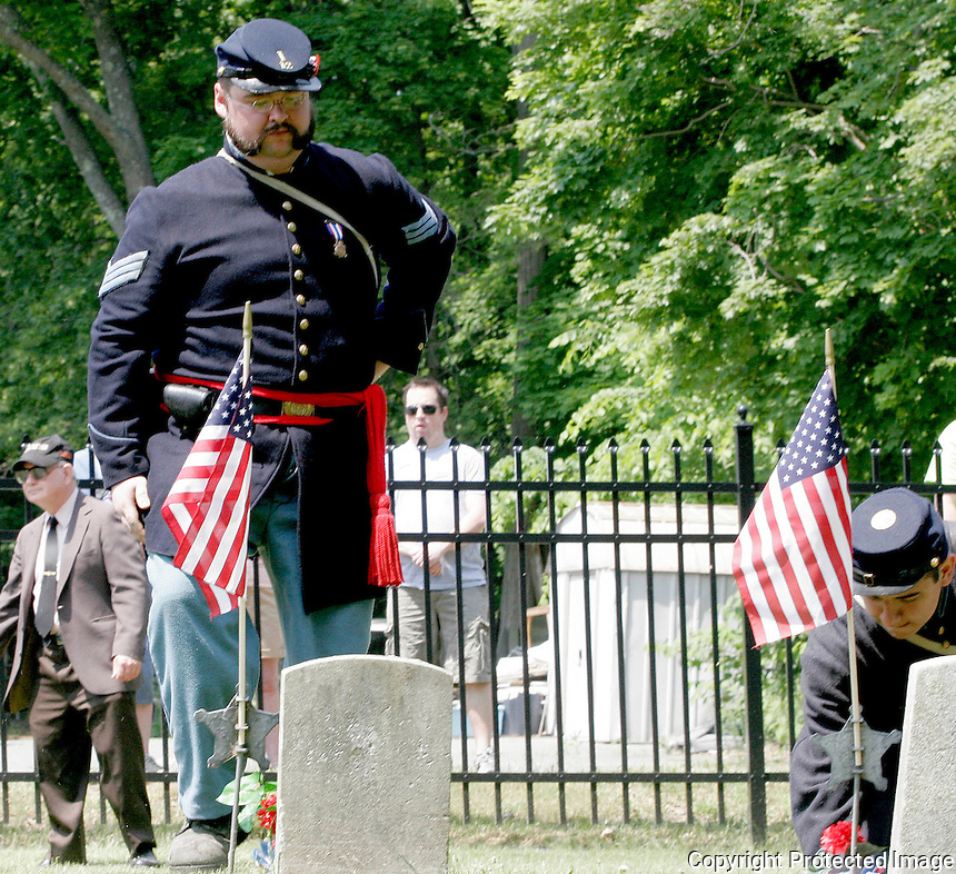 Mark Nickerson and Jeremiah Grossman put down a flower on a grave at Evergreen Cemetery during one of the Stoughton Memorial Day ceremonies in Stoughton on Monday. (Photo by Gary Wilcox).