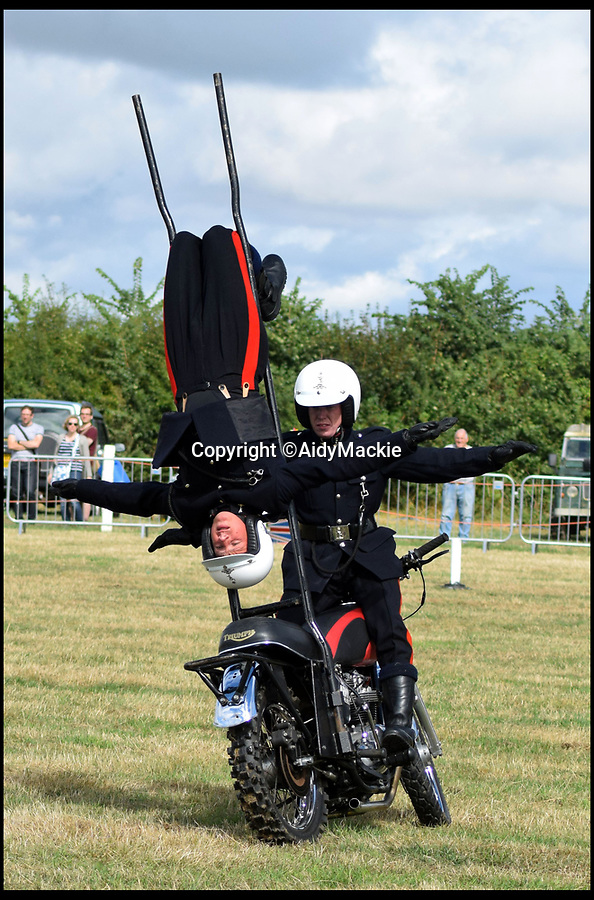 BNPS.co.uk (01202 558833)Pic: AidyMackie/BNPS<br /> <br /> Cpl Aidy Mackie (upside down)with his bike before the White Helmets were disbanded.<br /> <br /> A member of the Army's White Helmets has bought back his beloved bike after it went up for auction following the axing of the daring motorcycle display team.<br /> <br /> Corporal Aidy Mackie paid £11,200 for the Triumph machine that he couldn't bear to part with after the popular group was disbanded in August.<br /> <br /> The Army put six of the bikes up for auction in Dorset which Aidy, 31, attended and saw off rival bidders.