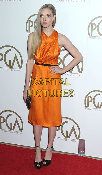Amanda Seyfried.At the 24th Annual Producers Guild Awards held at the Beverly Hilton Hotel, Beverly Hills, California, USA,.26th January 2013..PGAs PGA arrivals full length orange dress black belt draped cowl neck peep toe ankle strap sandals belt shoes clutch bag sleeveless hand on hip.CAP/ADM/RE.©Russ Elliot/AdMedia/Capital Pictures.