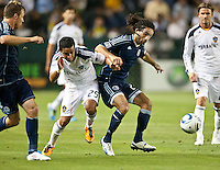 CARSON, CA – May 14, 2011: LA Galaxy forward Miguel Lopez (25) and Sporting KC midfielder Stephane Auvray (27) battle for the ball during the match between LA Galaxy and Sporting Kansas City at the Home Depot Center in Carson, California. Final score LA Galaxy 4, Sporting Kansas City 1.