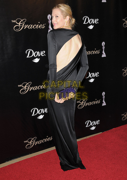 KELLY RUTHERFORD.The Gracie Awards Gala held at The Beverly Hilton Hotel in Beverly Hills, California, USA..May 25th, 2010           .full length dress black long sleeves maxi gold necklaces back behind rear slashed looking over shoulder clutch bag .CAP/RKE/DVS.©DVS/RockinExposures/Capital Pictures.