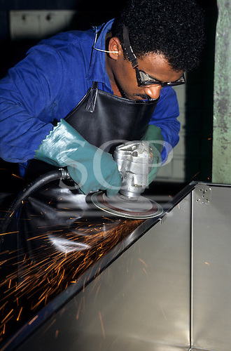 Sao Paulo, Brazil. Multibras factory; worker in blue with goggles finishing off a sheet steel assembly using a grinder.