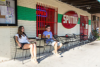Young attractive couple enjoys a cold beer at an Eastside restaurant on East 6th Street in East Austin.