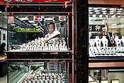 A shopkeeper places the luxury watches on the shop window in a store in Central Macau, China.