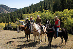 Family outdoors on a crisp and cool fall morning riding horses on a wrangler-led ride, amid aspen groves high in the Rocky Mountains, near Estes Park, Colorado, USA