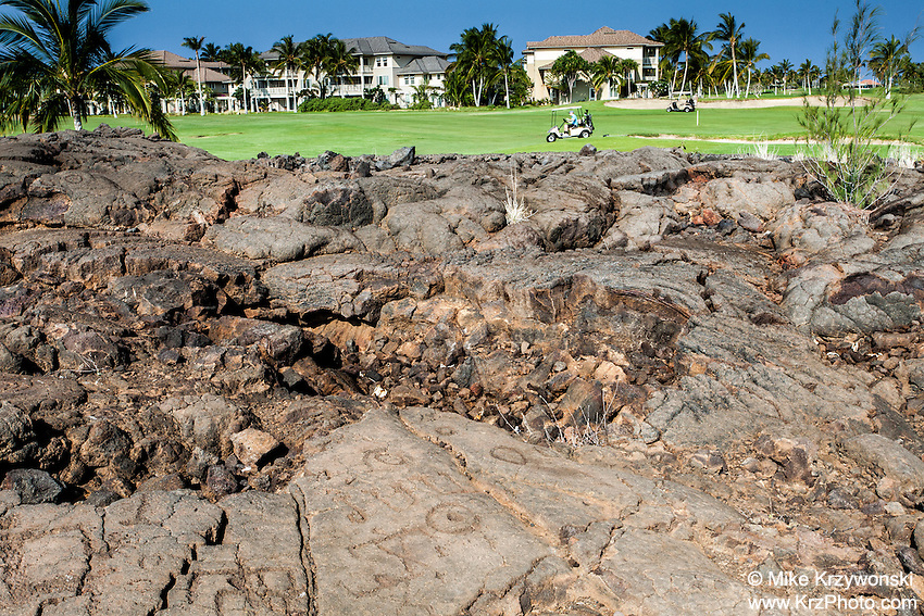 Petroglyphs w/ the King's Course golf course & condos in background at the Waikoloa Petroglyph Field, Big Island, Hawaii